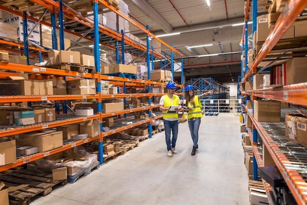 Dois trabalhadores do armazém caminhando na área de armazenamento de distribuição discutindo sobre logística e organização