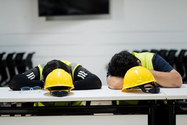 Dois trabalhadores dormem na mesa, trabalham duro, como um homem tão cansado