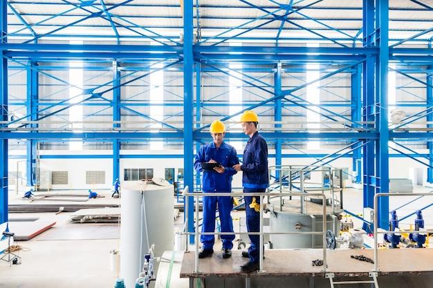 Dois trabalhadores em uma grande oficina de metal ou fábrica verificando o trabalho em uma grande máquina