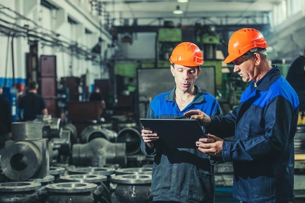Dois trabalhadores em uma planta industrial com um tablet na mão, trabalhando juntos nas atividades de manufatura