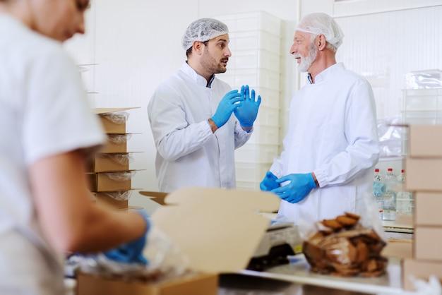 Dois trabalhadores em uniformes brancos estéreis embalando biscoitos e conversando enquanto estavam na fábrica de alimentos.