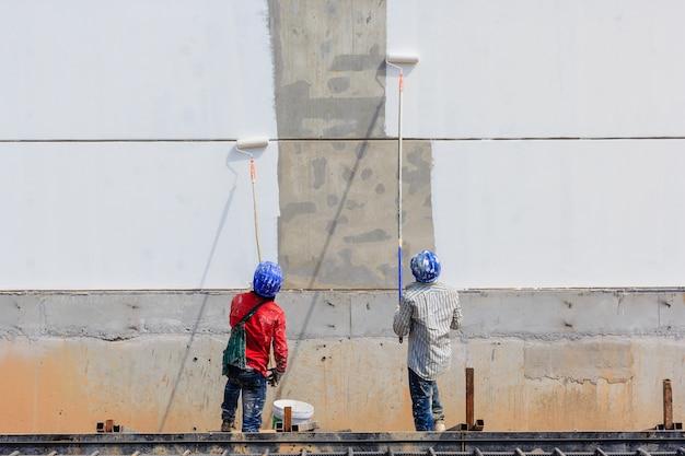Dois trabalhadores estão pintando a área em branco na parede