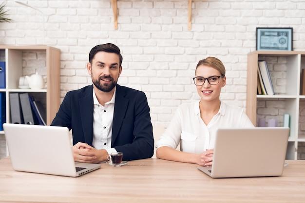 Dois trabalhadores estão sentados à mesa e trabalhando com um laptop.