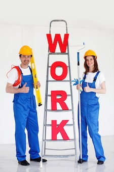 Dois trabalhadores na frente da escada com trabalho de palavra