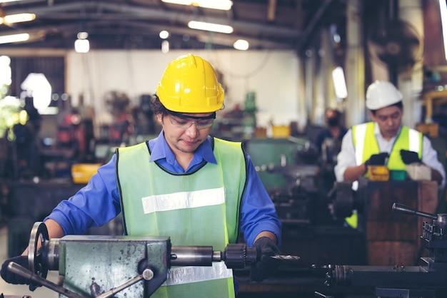 Dois trabalhadores na planta de produção como equipe discutindo, cena industrial em segundo plano, trabalhando juntos nas atividades de fabricação