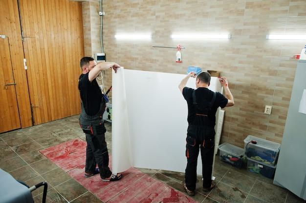 Dois trabalhadores no detalhamento da garagem seguram uma capa de filme anti-cascalho de poliuretano para o carro.
