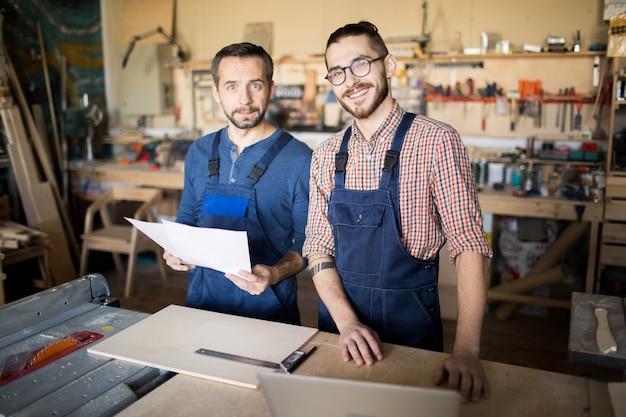 Dois trabalhadores posando na loja de madeira