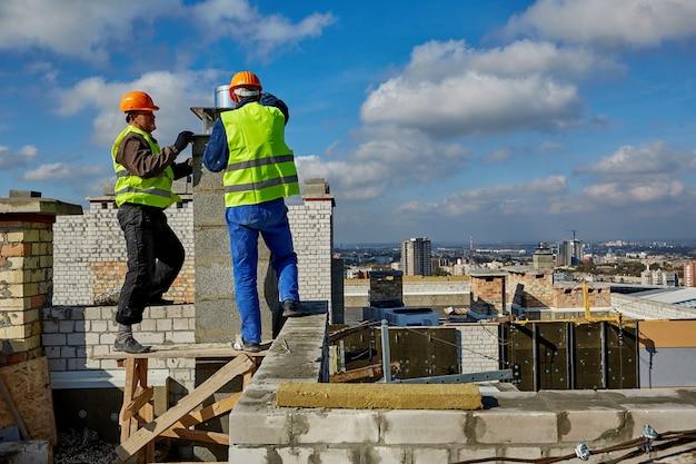 Dois trabalhadores profissionais do sexo masculino com roupas de proteção e capacetes estão trabalhando com sistema de ventilação no telhado de um prédio em construção