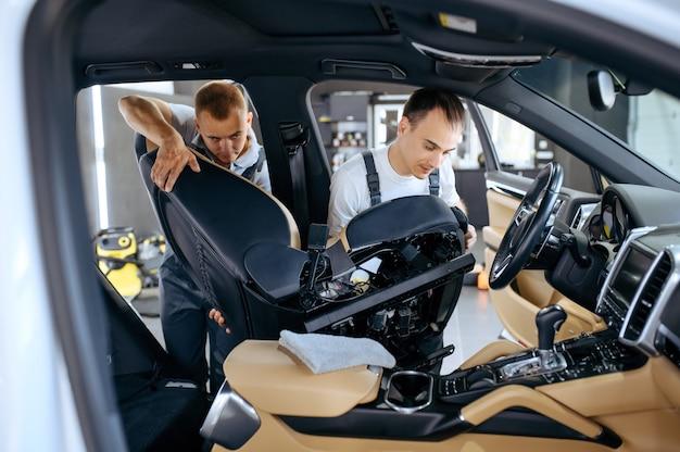 Dois trabalhadores removem assentos de carro para lavagem a seco e detalhamento