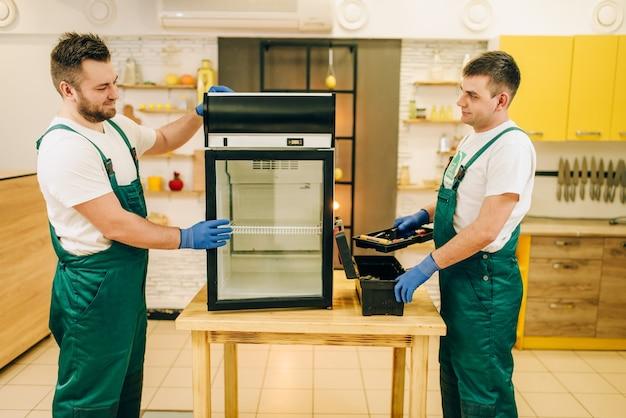 Dois trabalhadores uniformizados consertam geladeira em casa