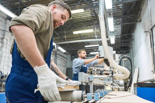 Dois trabalhadores usando a máquina na loja de marcenaria