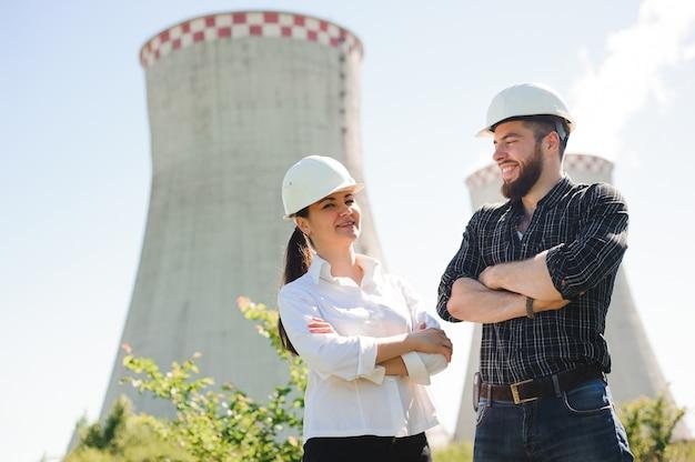 Dois trabalhadores usando capacete protetor trabalham com energia elétrica