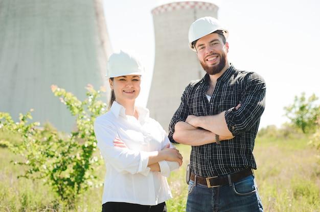 Dois trabalhadores usando capacete protetor trabalham na usina elétrica