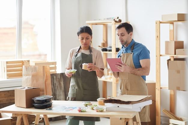 Dois trabalhadores vestindo aventais empacotando pedidos em pé perto da mesa de madeira, serviço de entrega de comida