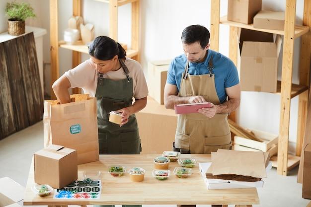 Dois trabalhadores vestindo aventais empacotando pedidos em uma mesa de madeira em um serviço de entrega de comida