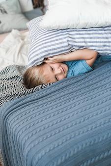 Dois travesseiros, sobre, a, sorrindo, menino, encontrar-se cama