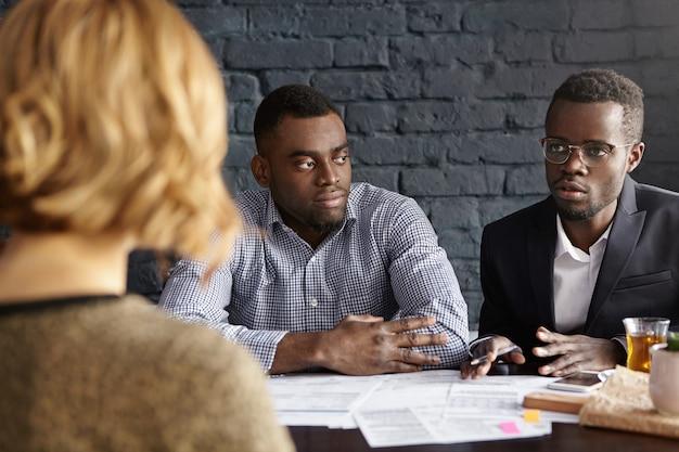 Dois tristes executivos de pele escura se reunindo com uma mulher irreconhecível