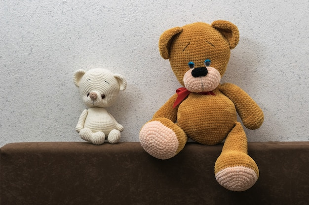 Dois tristes filhotes de urso de malha no sofá contra a parede de luz. lindo brinquedo de malha.