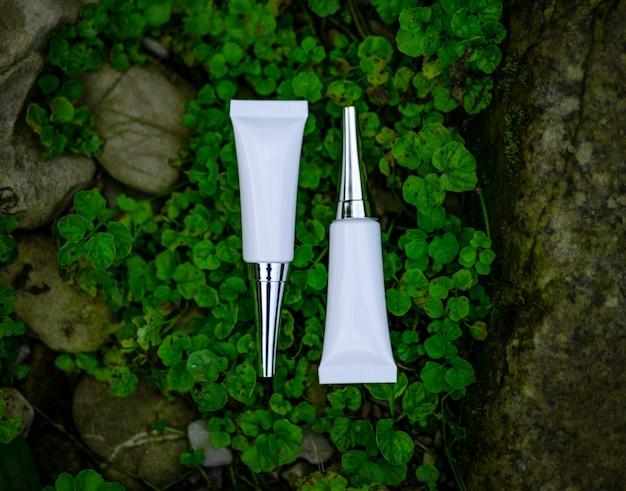 Dois tubos cosméticos brancos paralisam um ao outro na grama