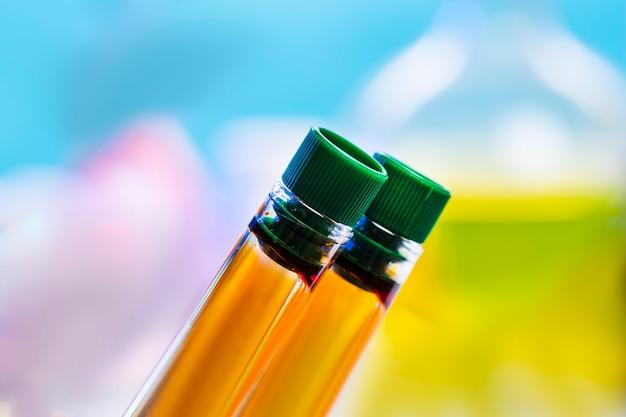Dois tubos de ensaio químico com tampas fechadas com um líquido laranja em uma superfície azul