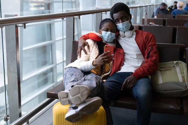 Dois turistas africanos usam máscaras e sentam-se juntos em uma cadeira no aeroporto esperando o voo