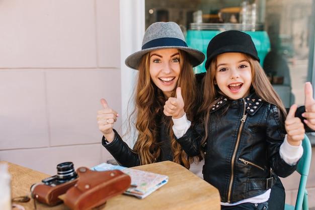 Dois turistas animados, posando no restaurante ao ar livre com polegares para cima, esperando o almoço após a caminhada.