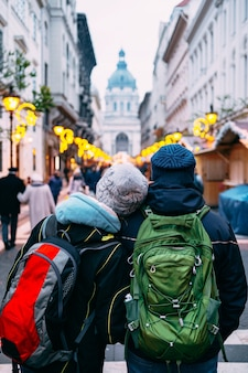 Dois turistas com mochilas percorrem as ruas de budapeste, decoradas para o natal, tendo como pano de fundo a basílica de santo estêvão.