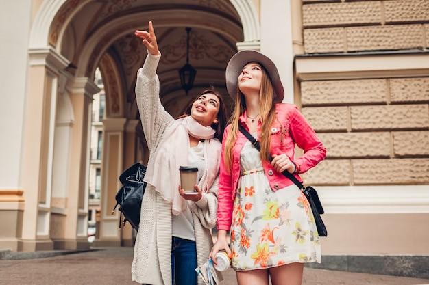 Dois turistas das mulheres que falam ao ir sightseeing em odessa. felizes amigos viajantes apontando para cima