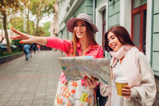 Dois turistas das mulheres que procuram pela maneira direita usando o mapa em odessa. felizes amigos viajantes mostrando direção