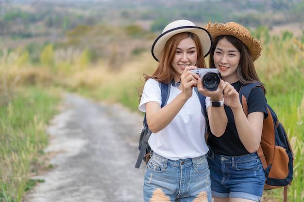 Dois turistas mulher tirando uma foto com a câmera na natureza