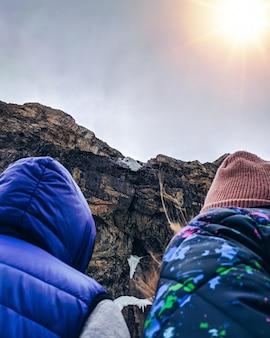 Dois turistas que apreciam o por do sol sobre uma montanha.