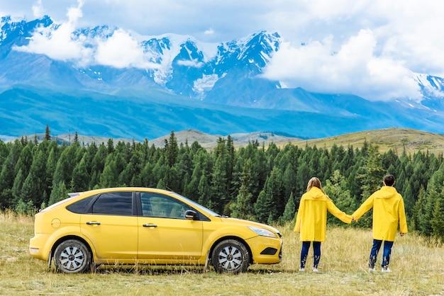 Dois turistas, um homem e uma mulher perto do carro, no fundo de montanhas em viagem