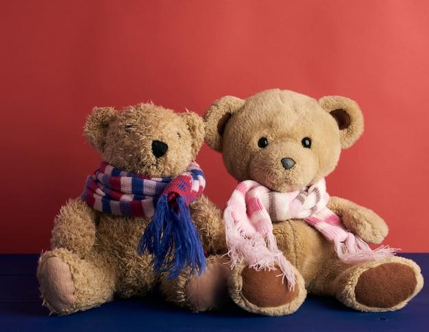 Dois ursos de pelúcia em lenços estão sentados sobre um fundo vermelho