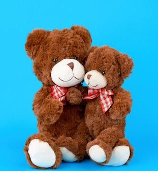 Dois ursos de pelúcia marrons com laços amarrados ao pescoço, um ursinho sentado nos braços de um grande