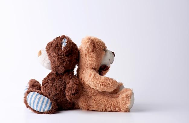 Dois ursos de pelúcia marrons sentam-se em uma superfície branca de costas