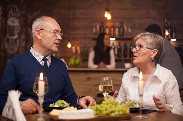 Dois velhos amigos na casa dos 60 anos conversando sobre o que têm feito ultimamente durante um jantar em um restaurante