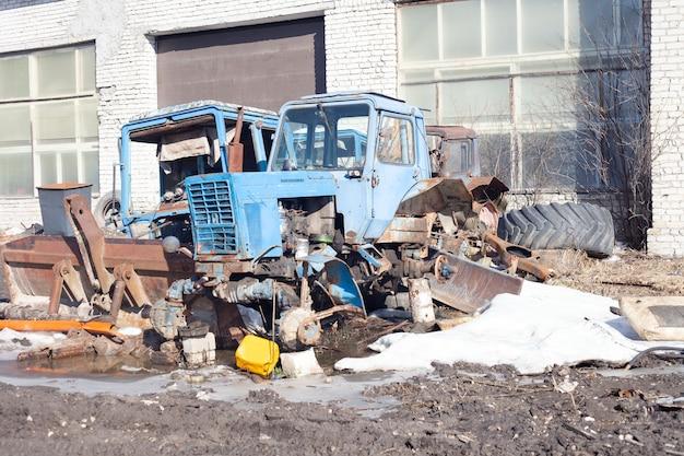 Dois velhos tratores azuis quebrados ficam do lado de fora na primavera.