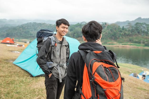 Dois viajantes asiáticos em pé perto do lago