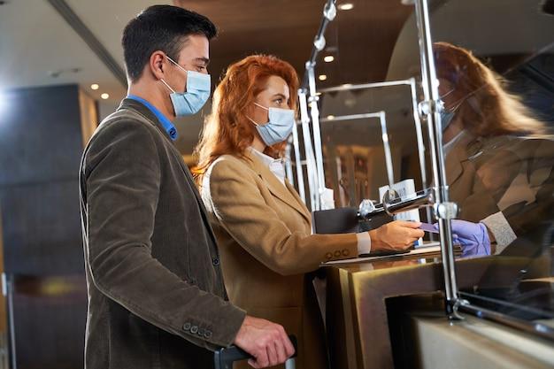 Dois viajantes com máscaras médicas em pé na recepção do hotel e uma mulher entregando seu cartão de crédito ao administrador