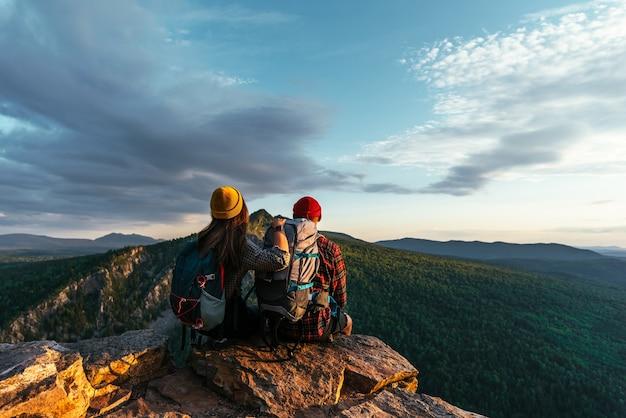 Dois viajantes estão sentados na beira de um penhasco admirando a bela vista panorâmica. um casal apaixonado em uma rocha admira as belas paisagens. viajantes nas montanhas ao pôr do sol. copie o espaço