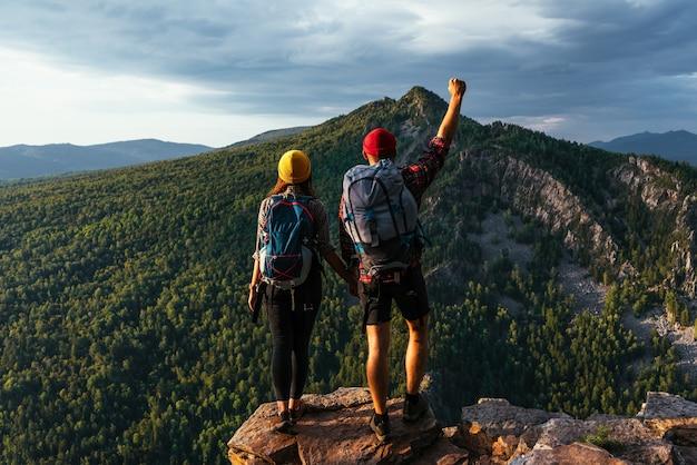 Dois viajantes felizes com mochilas no topo da montanha. dois turistas com mochilas apreciam o pôr do sol do alto da montanha. viaje com uma mochila. férias nas montanhas