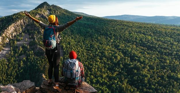 Dois viajantes no fundo das montanhas, panorama. viajantes ao pôr do sol nas montanhas. turistas com mochilas na beira da falésia. um casal admira o pôr do sol de um penhasco. copie o espaço