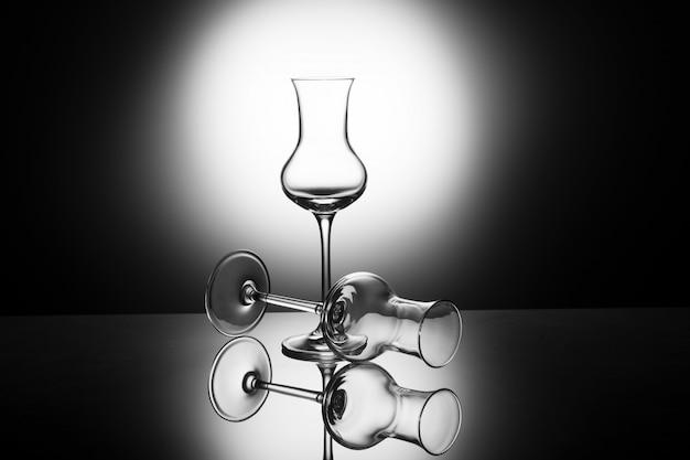 Dois vidros de tiro elegantes bonitos do grappa no luminoso, conceito do vidro vazio
