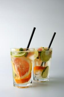 Dois vidros do cocktail caseiro do verão frio com limão, cal, laranja e pamplumossa.