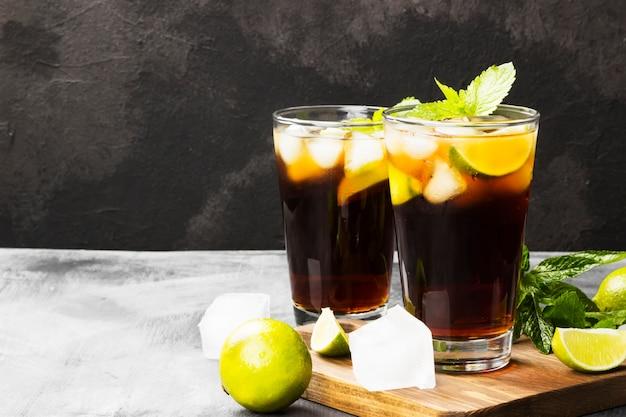 Dois vidros do cocktail cuba libre em um fundo escuro. copie o espaço. fundo de alimentos