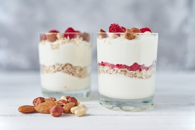 Dois vidros do granola grego do iogurte com framboesas, flocos da farinha de aveia e porcas em um fundo branco. nutrição saudável