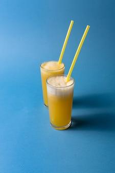 Dois vidros do suco de fruta do abacaxi sobre o fundo colorido azul.