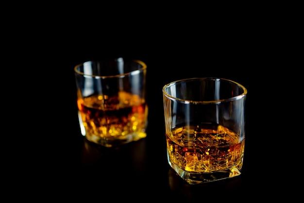 Dois vidros do uísque ou do uísque com gelo no fundo preto.