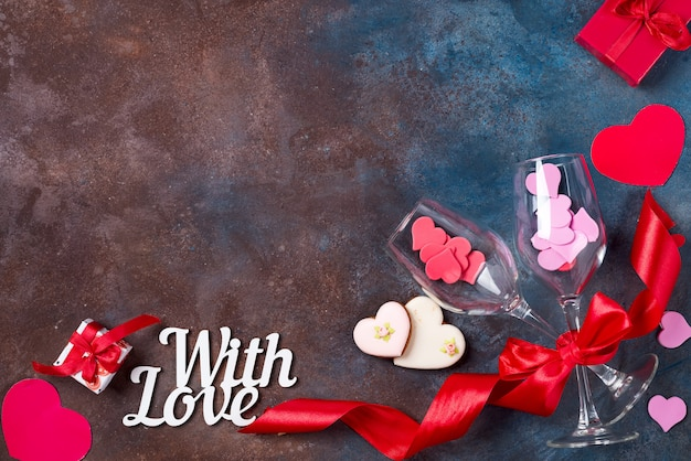Dois vidros do vinho, corações dos bolinhos no fundo de pedra. dia dos namorados
