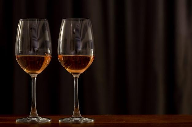 Dois vidros do vinho de rosa na tabela de madeira para comemorar para um par.